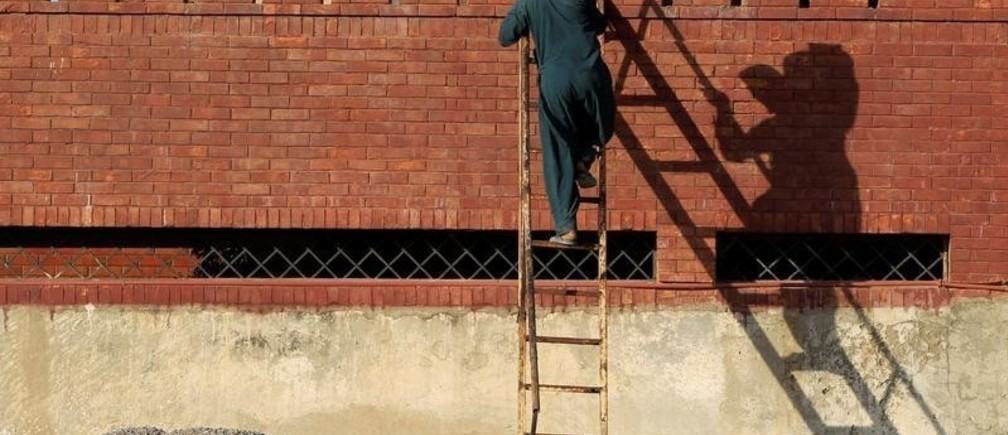 A laborer carries a sack of gravel up a ladder to the roof of a house under construction in Islamabad, Pakistan May 26,  2017. REUTERS/Caren Firouz     TPX IMAGES OF THE DAY - RC1B94269D60
