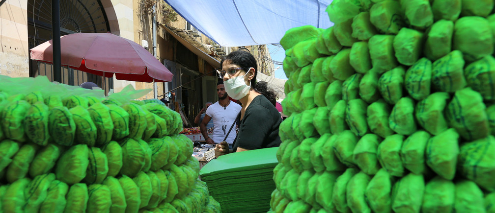 A woman wearing a face mask walks past sweets for sale, ahead of the upcoming holiday of Eid al-Fitr marking the end of Ramadan, amid concerns over the spread of coronavirus disease (COVID-19), in Sidon, southern Lebanon May 21, 2020. REUTERS/Aziz Taher - RC21TG9IU7D9