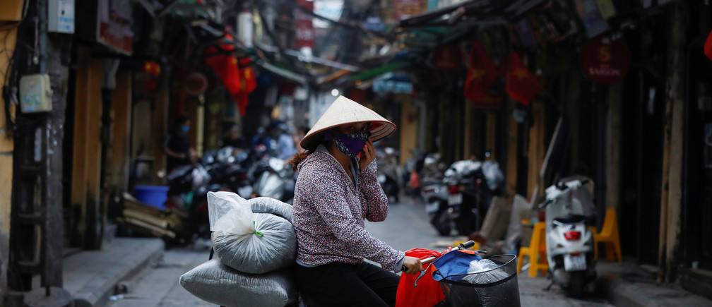 A woman wears a protective mask as she rides past an empty street during the coronavirus disease (COVID-19) outbreak in Hanoi, Vietnam March 26, 2020. vietnam nviet nam asia Coronavirus china virus health healthcare who world health organization disease deaths pandemic epidemic worries concerns Health virus contagious contagion viruses diseases disease lab laboratory doctor health dr nurse medical medicine drugs vaccines vaccinations inoculations technology testing test medicinal biotechnology biotech biology chemistry physics microscope research influenza flu cold common cold bug risk symptomes respiratory china iran italy europe asia america south america north washing hands wash hands coughs sneezes spread spreading precaution precautions health warning covid 19 cov SARS 2019ncov wuhan sarscow wuhanpneumonia  pneumonia outbreak patients unhealthy fatality mortality elderly old elder age serious death deathly deadly