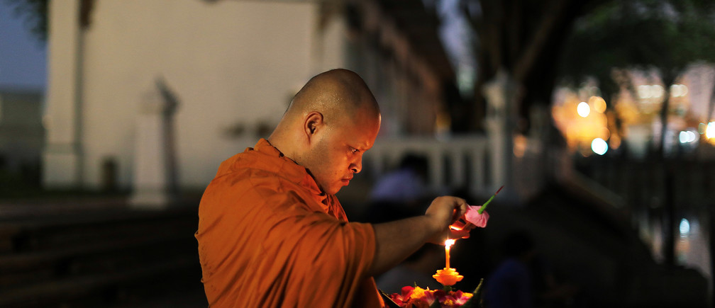 A Buddhist monk prays before casting krathongs into a pond in a public park during the Loy Krathong festival which is held as a symbolic apology to the goddess of the river in Bangkok, Thailand, November 22, 2018. REUTERS/Jorge Silva - RC1187A0D580