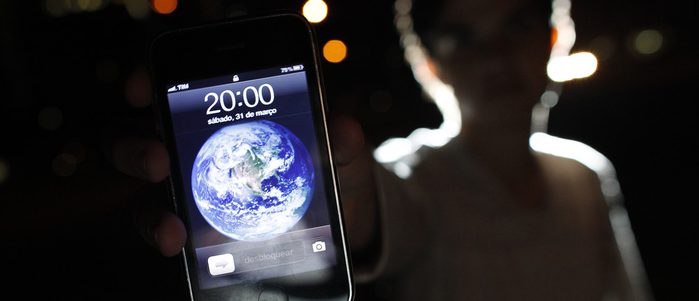 A man poses with an iPhone during Earth Hour in the center of Brasilia March 31, 2012.