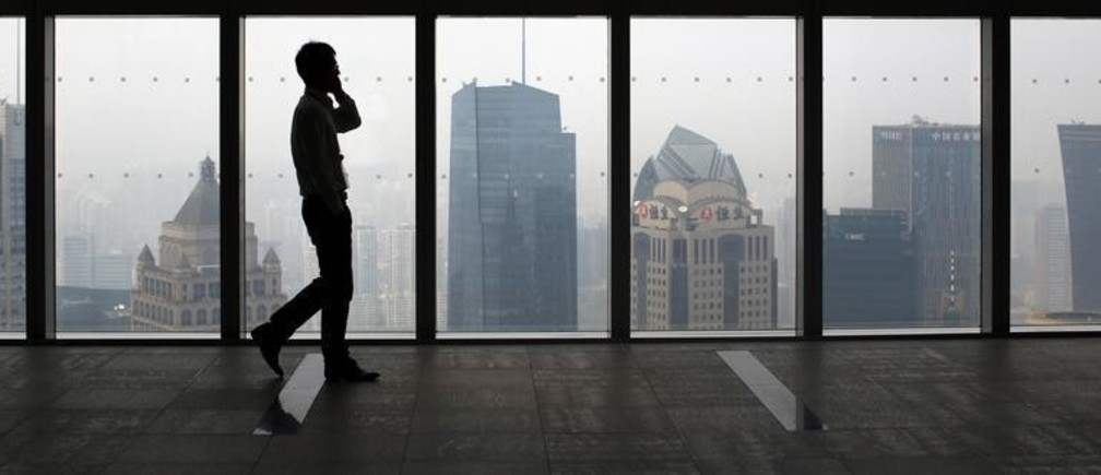 A man talks on a mobile phone as he walks past the view of the Shanghai skyline, September 4, 2014. Companies facing antitrust probes in China are subject to a host of pressure tactics from regulators, a business lobby said, in the latest report to cite due process concerns over China's anti-monopoly enforcement. REUTERS/Carlos Barria  (CHINA - Tags: BUSINESS POLITICS CITYSCAPE) - GM1EA9416MF01