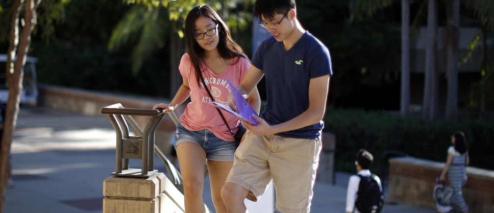 Economics major Hazel Ho, 21, (L) and math major Vincent Yeung, 21, walk on campus as around 12,000 new University of California, Los Angeles (UCLA) students move into campus residence halls in preparation for the new school year beginning October 2, in Los Angeles, California September 25, 2014.