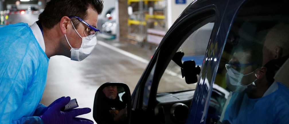 Biologist Jerome De Marchin talks to a patient while he sits in his car at a drive-in testing site for coronavirus (COVID-19) at the Regional Hospital Center in Liege, Belgium March 11, 2020.  REUTERS/Francois Lenoir - RC2QHF9ZUPDS