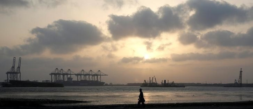 A man is silhouetted as he walks amid hot and humid weather at breakwater along port area in Karachi, Pakistan May 7, 2018. REUTERS/Akhtar Soomro