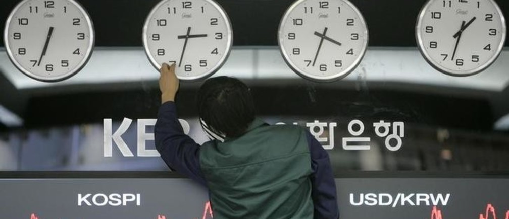 A worker adjusts clocks displaying the time in London, Hong Kong, Seoul and New York as screens (bottom) show the composite price index of stocks (L) and exchange rates between the U.S. dollar and the Korean won at a dealing room of the Korea Exchange Bank in Seoul December 15, 2008. Asian stocks climbed nearly 4 percent on Monday on renewed hopes the U.S. automaker industry would be rescued, strengthening willingness to take risks and knocking the U.S. dollar to a two-month low against the euro. South Korea's benchmark KOSPI .KS11 share average was up 4.9 percent.