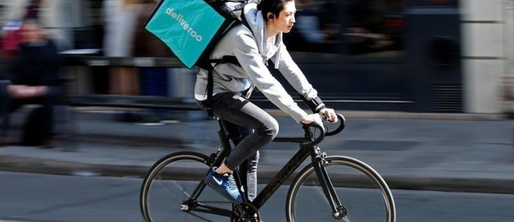 A cyclist rides a bicyle as he delivers food for Deliveroo, an example of the emergence of what is known as the 'gig economy', in Paris, France, April 7, 2017. Picture taken April 7, 2017. REUTERS/Charles Platiau - RC153FF13360