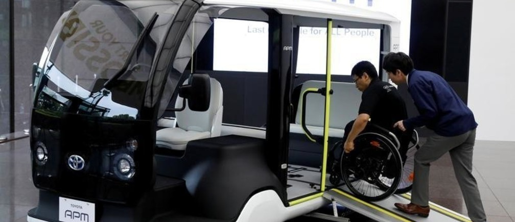 An employee of Toyota Motor Corp. demonstrates APM (Accessible People Mover), a mobility vehicle designed expressly for use at the Tokyo 2020 Olympic and Paralympic Games, during a press preview in Tokyo, Japan July 18, 2019. Picture taken July 18, 2019.  REUTERS/Issei Kato - RC1982868A90
