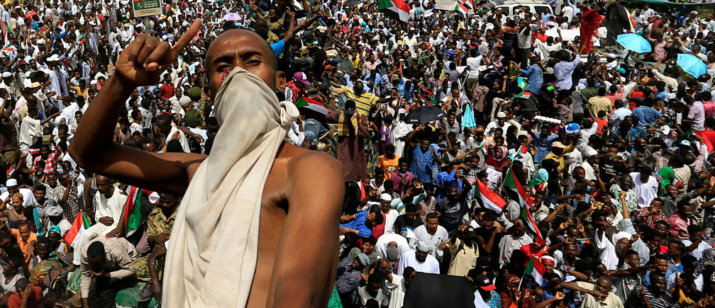 A Sudanese demonstrator gestures while riding atop a military truck as he protests against the army's announcement that President Omar al-Bashir would be replaced by a military-led transitional council, near Defence Ministry in Khartoum, Sudan April 12, 2019. REUTERS/Stringer TPX IMAGES OF THE DAY - RC182AC5A0D0