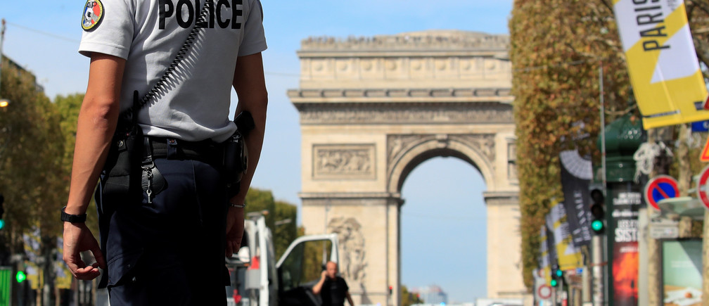 French police stand as Paris police bomb squad inspect a car in Champs Elysees avenue in Paris, France, September 16, 2018. REUTERS/Gonzalo Fuentes - RC1C8FE01740