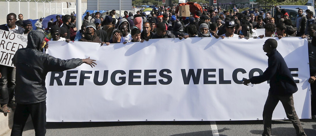 "Migrants and refugees hold a banner which reads, ""Refugees Welcome"" with members of refugee aid organisations in the encampment known as the ""New Jungle"" during a demonstration of solidarity in Calais, France, September 19, 2015. French authorities say more than 3,000 people fleeing war and poverty in the Middle East, Africa and Asia now live in the jungle, with most trying to find a way to cross to England. REUTERS/Regis Duvignau - RTS1VPV"