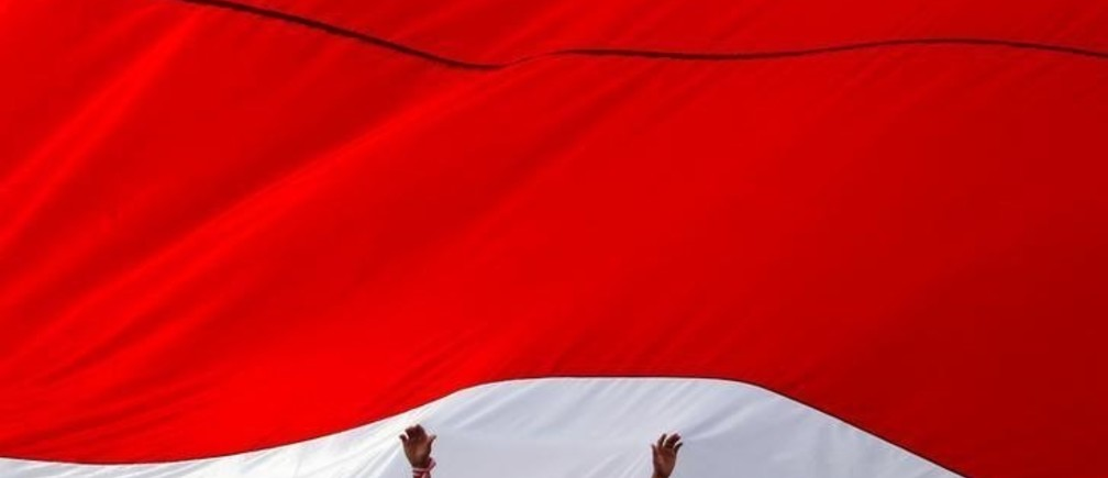 A man touches a large Indonesian flag as he takes part in a rally against what organisers see as growing racial and religious intolerance in the world's largest Muslim-majority country, in Jakarta, Indonesia November 19, 2016. REUTERS/Iqro Rinaldi     TPX IMAGES OF THE DAY