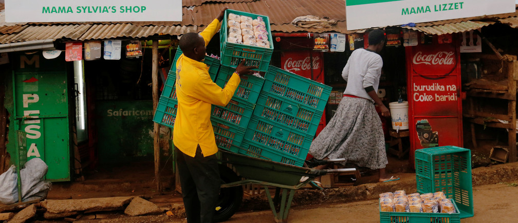 A man arranges crates of bread outside a shop at the end of a night-long curfew ordered by Kenya's President Uhuru Kenyatta to slow the spread of the coronavirus disease (COVID-19), in Nairobi, Kenya March 28, 2020. REUTERS/Thomas Mukoya - RC2USF95CJKV