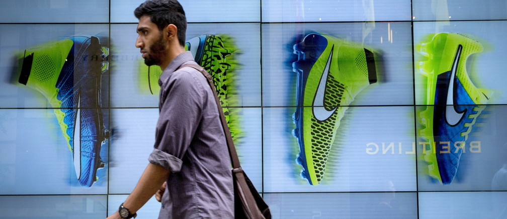A man passes by the Niketown store in midtown Manhattan in New York June 25, 2015. Nike Inc, the world's largest footwear maker, reported a better-than-expected profit for the eighth quarter in a row as it sold more high margin basketball shoes and apparel at higher prices.