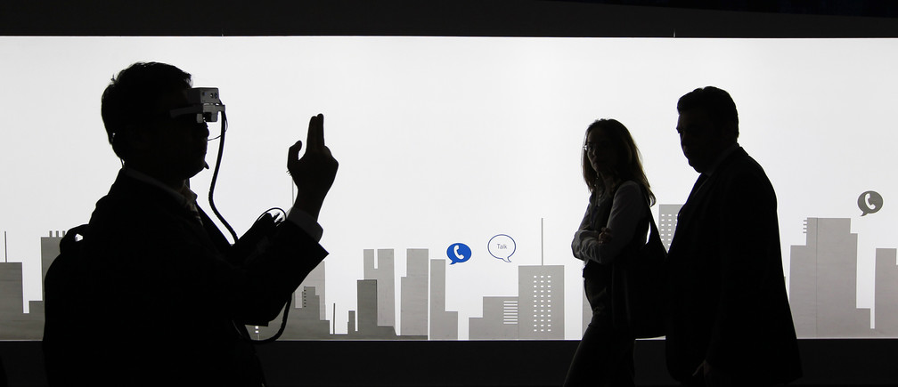 ilhouettes of visitors are seen in front of a drawing of the city skyline at the Mobile World Congress at Barcelona, February 27, 2013.