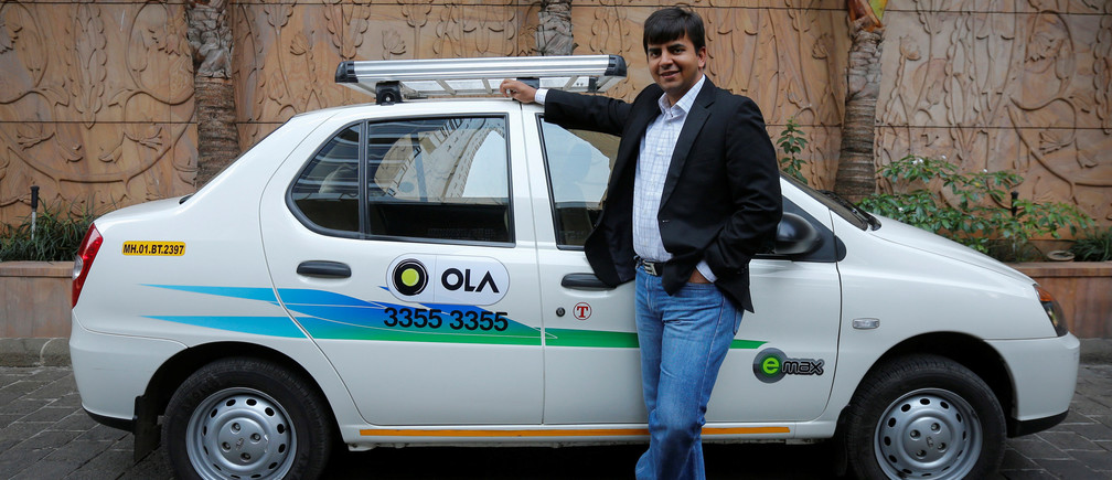 Bhavish Aggarwal, CEO and co-founder of Ola, an app-based cab service provider, poses in front of one of the company's vehicles..