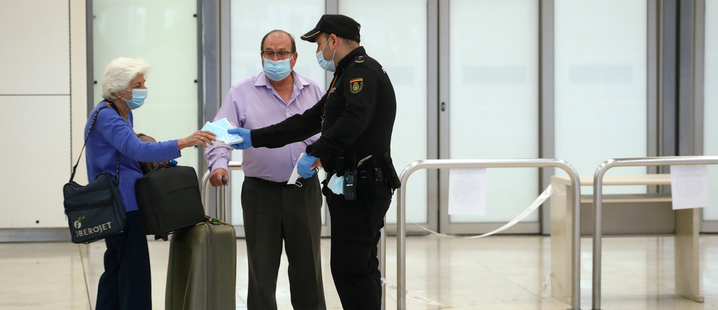 Los pasajeros recogen máscaras faciales de protección de un oficial de la Policía Nacional al llegar al aeropuerto Adolfo Suárez Barajas, después de que el gobierno español anunciara que a partir del 15 de mayo todas las personas que entren en España tendrán que estar en cuarentena durante dos semanas, en medio del brote de la enfermedad coronavirus (COVID-19) en Madrid, España, el 12 de mayo de 2020.   Traducción realizada con la versión gratuita del traductor www.DeepL.com/Translator