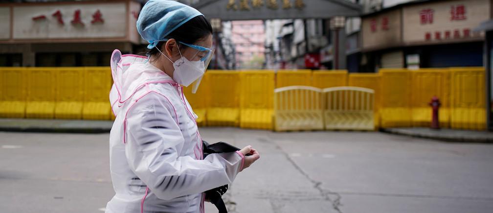 Una mujer con una máscara facial camina en una zona residencial bloqueada por barreras en Wuhan, provincia de Hubei, el epicentro del brote de la enfermedad coronavirus de China (COVID-19), el 3 de abril de 2020.