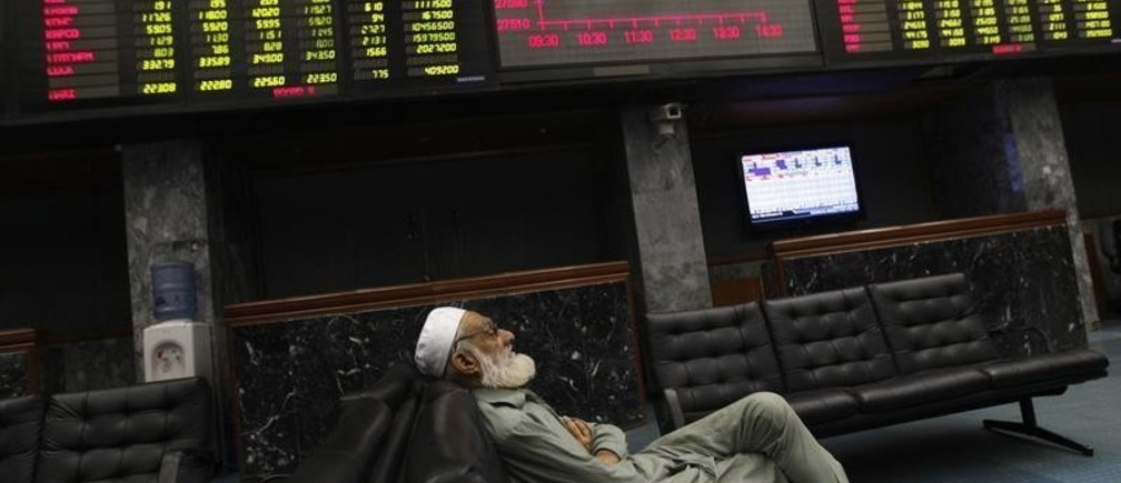 A man takes a nap on a couch under an electronic board displaying share prices during trading session at the Karachi Stock Exchange April 2, 2014. Pakistan's main stock exchange closed higher on Wednesday, with the benchmark 100-share index of the Karachi Stock Exchange rising 1.33 percent, or 366.52 points to 27,932.02.