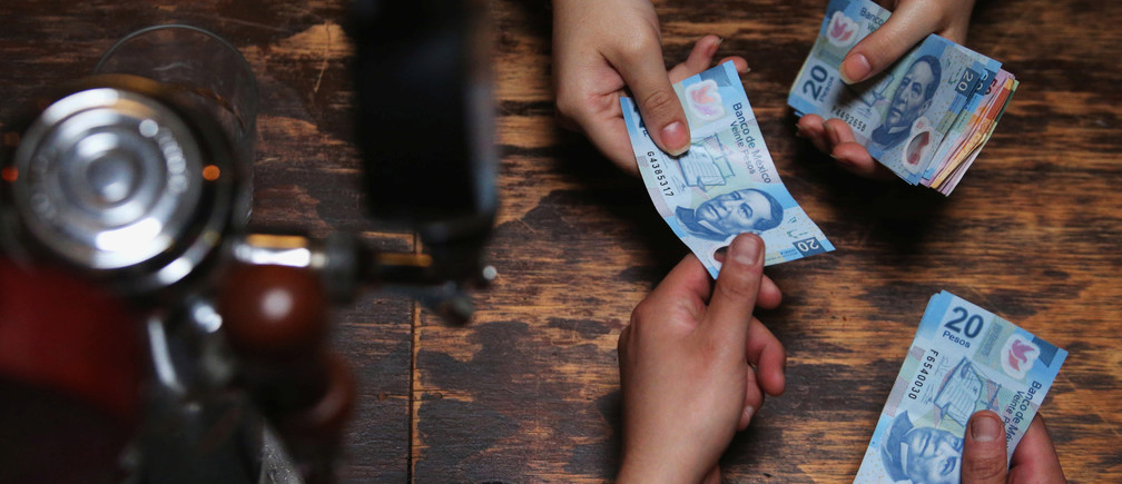 A buyer and seller exchange Mexican pesos in a restaurant in Mexico City, Mexico, August 3, 2017. REUTERS/Edgard Garrido - RTS1ABP2