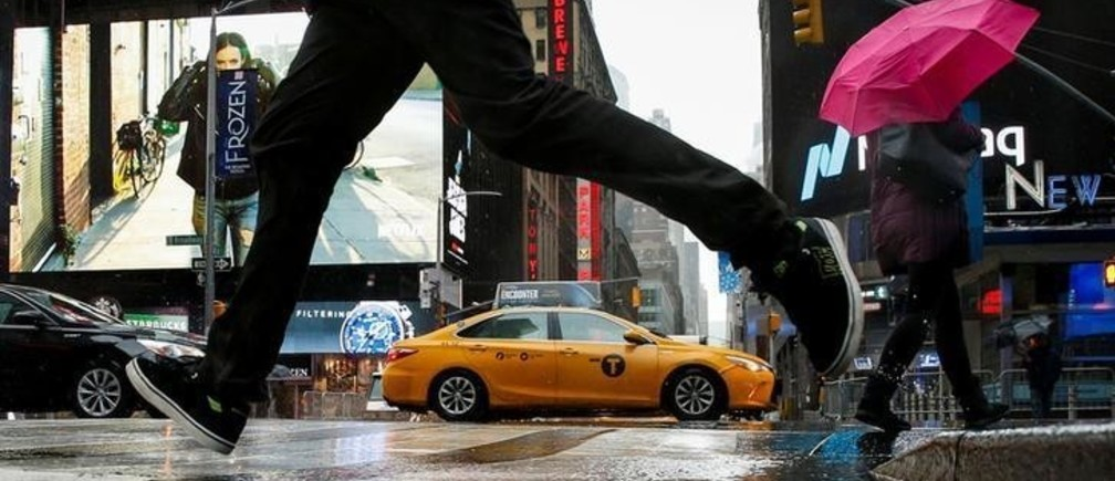 A man jumps over a puddle in Times Square during a winter nor'easter in New York City, U.S., March 2, 2018. REUTERS/Brendan McDermid