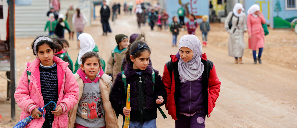Syrian refugee children walk to the school during rainy weather at the Al Zaatari refugee camp in the Jordanian city of Mafraq, near the border with Syria December 18, 2016. REUTERS/Muhammad Hamed - RTX2VJMJ