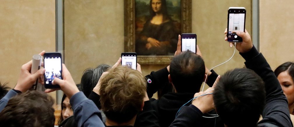 Visitors take pictures of the Mona Lisa by Leonardo da Vinci at the Louvre museum in Paris.