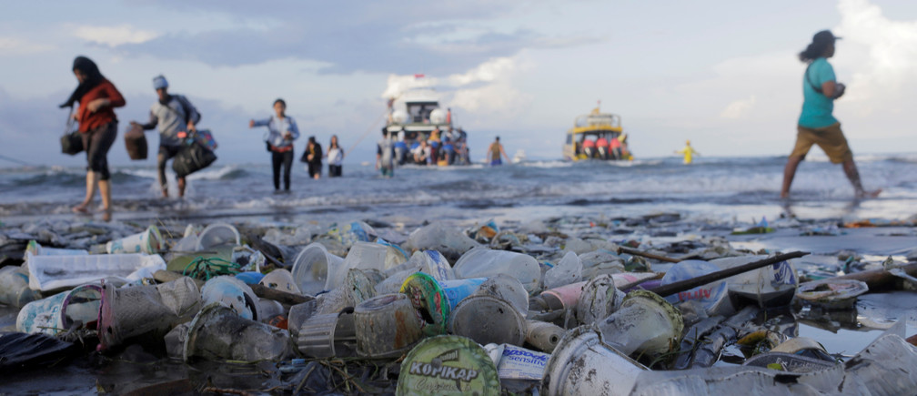 Tourists and local residents disembark a boat coming from nearby Nusa Penida island as plastic trash pollutes the beach in Sanur, Denpasar, Bali, Indonesia April 10, 2018. REUTERS/Johannes P. Christo     TPX IMAGES OF THE DAY - RC1DEFD78A90