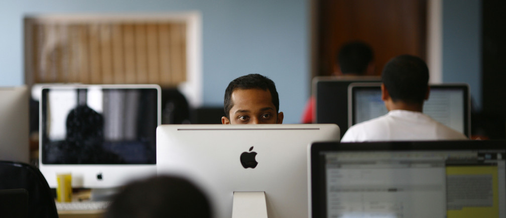 An employee works on his computer at the office of CloudFactory, a Canadian startup that based itself in Kathmandu, where it hires teams of Nepalese October 5, 2012. Not far from the world of regimented cubicles and headset-toting call centre operators, a quiet revolution is stirring in its slippers. While it's early days, proponents of so-called commercial crowdsourcing contend that a swelling army of global freelancers is already disrupting traditional outsourcing - from preparing tax statements to conducting research on pediatricians. Picture taken October 5, 2012. To match story ASIA-FREELANCE/       REUTERS/Navesh Chitrakar (NEPAL) - RTR39016