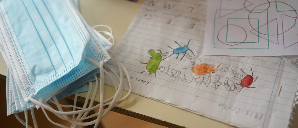 Las máscaras y el trabajo de clase se ven en el escritorio de un estudiante de la Escuela 30, una escuela rural que ha reanudado las clases después de un mes de descanso debido a la enfermedad coronavirus (COVID-19), en San José, Uruguay, el 22 de abril de 2020.