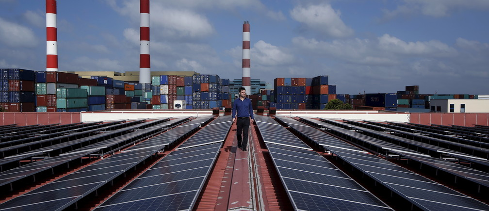 Sun Electric's Chief Executive Officer Matthew Peloso walks along rows of rooftop solar panels, operated under the company's SolarSpace energy retail programme at a factory in Singapore February 29, 2016.