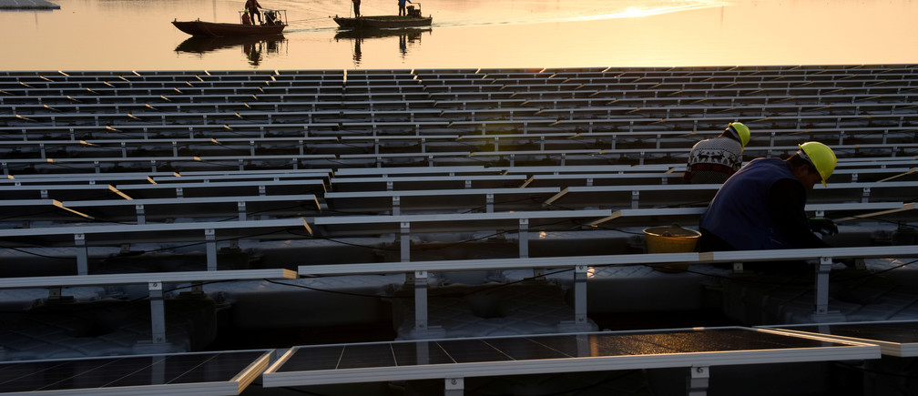 Workers install solar panels at a floating solar plant developed by China's Three Gorges Group, in Huainan, Anhui province, China December 11, 2017. Picture taken December 11, 2017. REUTERS/Stringer ATTENTION EDITORS - THIS IMAGE WAS PROVIDED BY A THIRD PARTY. CHINA OUT. - RC1B1F2115F0