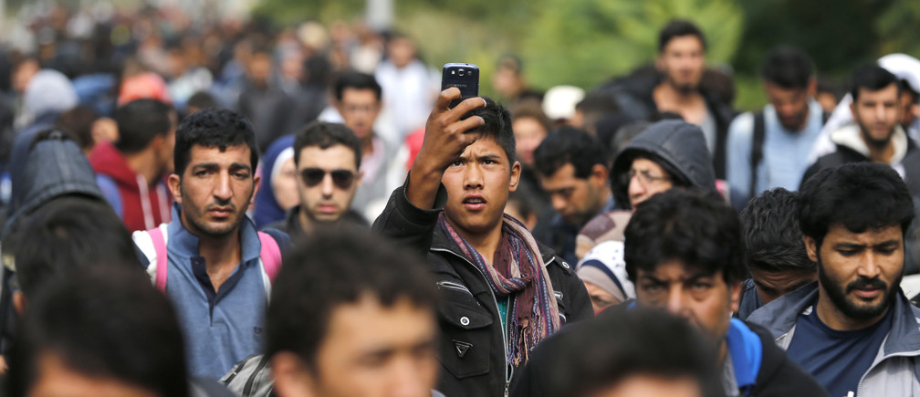 A migrant takes a picture with a mobile phone as he and others walk towards the Hungarian border after arriving at the train station in Botovo, Croatia September 24, 2015. Almost 50,000 migrants have flowed into European Union-member Croatia via Serbia in little over a week since Hungary, northern neighbour to both countries, barred their entry to the EU by sealing its border with Serbia with a metal fence. Croatia is sending the migrants north across its border with Hungary, which passes them on to Austria, but Zagreb says it cannot cope with the pace, leading to desperate and sometime angry scenes at over-crowded camps and railway stations. REUTERS/Antonio Bronic  - LR2EB9O12LN4R