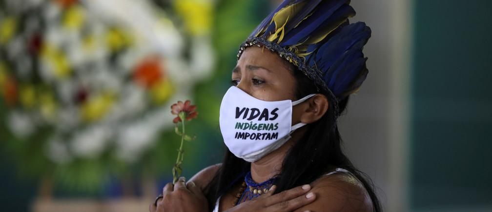 """Una mujer indígena, con una máscara facial que dice """"Las vidas de los indígenas importan"""", reacciona durante el funeral del Jefe Messias Kokama, de 53 años, del Parque das Tribos, que falleció debido a la enfermedad coronavirus (COVID-19), en el Parque das Tribos de Manaus, Brasil, el 14 de mayo de 2020."""