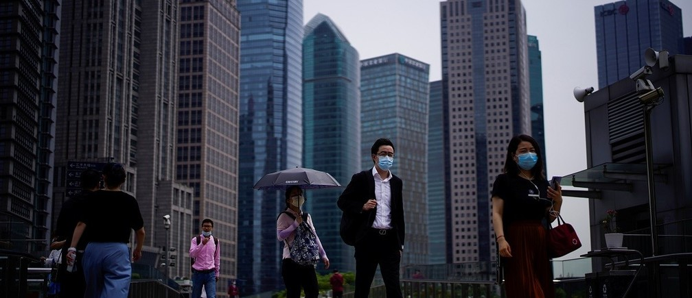 People wearing protective face masks walk past office buildings in Lujiazui financial district in Pudong, in Shanghai, following the coronavirus disease (COVID-19) outbreak, China June 4, 2020. REUTERS/Aly Song - RC2F2H9XOJG3