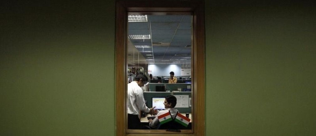 Employees are pictured through a window as they work on the floor of the outsourcing company WNS in Mumbai March 19, 2012. Indian back-office company WNS Holdings Ltd may launch the first of three customer-service centres in the United States over the next quarter, its CEO Keshav Murugesh said, as it looks to boost revenues in its second largest market. REUTERS/Vivek Prakash (INDIA - Tags: BUSINESS EMPLOYMENT) - GM1E83J1P3701