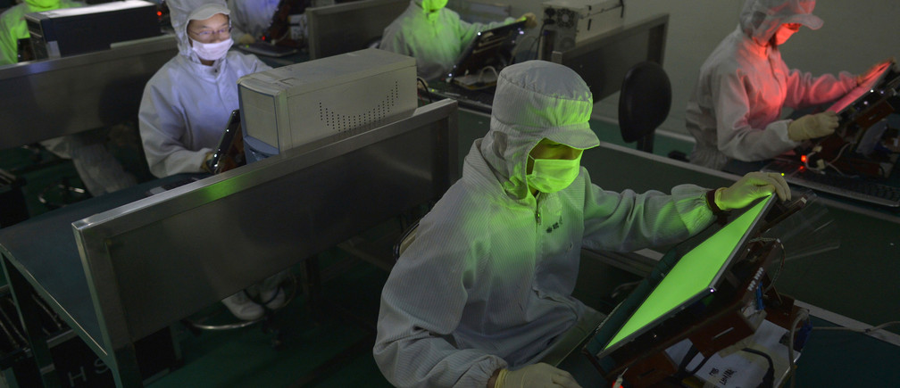 Employees work inside a LCD factory in Wuhan, Hubei province, May 8, 2013. Chinese flat screen makers, once dismissed as second-class players in the global LCD market, are drawing envious looks from big names such as LG Display Co Ltd and Samsung. While the Korean giants were busy developing next-generation organic light emitting diode (OLED) TVs, little-known Chinese companies have started selling a type of display that are sharper than the standard LCD and cheaper than OLED. Picture taken May 8, 2013. REUTERS/China Daily (CHINA - Tags: BUSINESS) CHINA OUT. NO COMMERCIAL OR EDITORIAL SALES IN CHINA - GM1E99H0ERL01