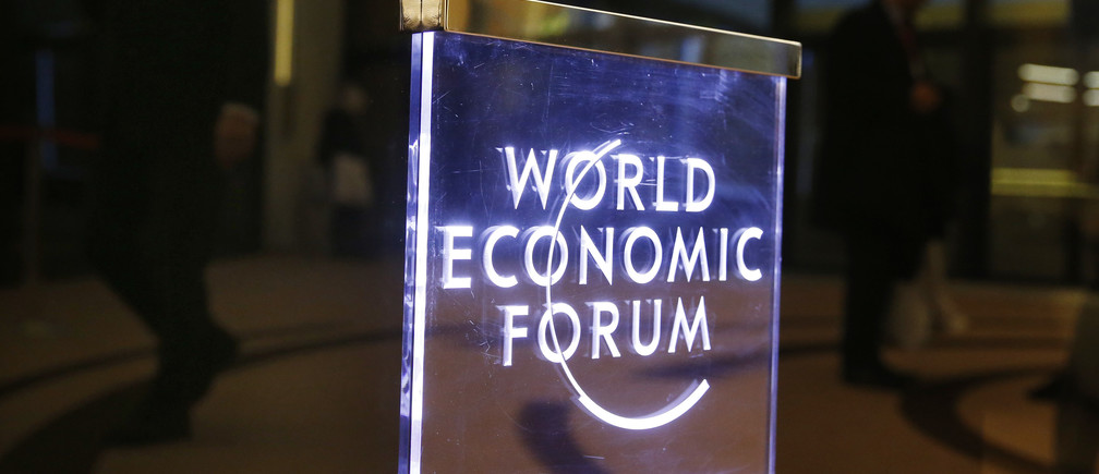 Attendees walk past a sign in the Congress Hall during the annual meeting of the World Economic Forum (WEF) in Davos, Switzerland, January 17, 2017. REUTERS/Ruben Sprich - RTSVXVE