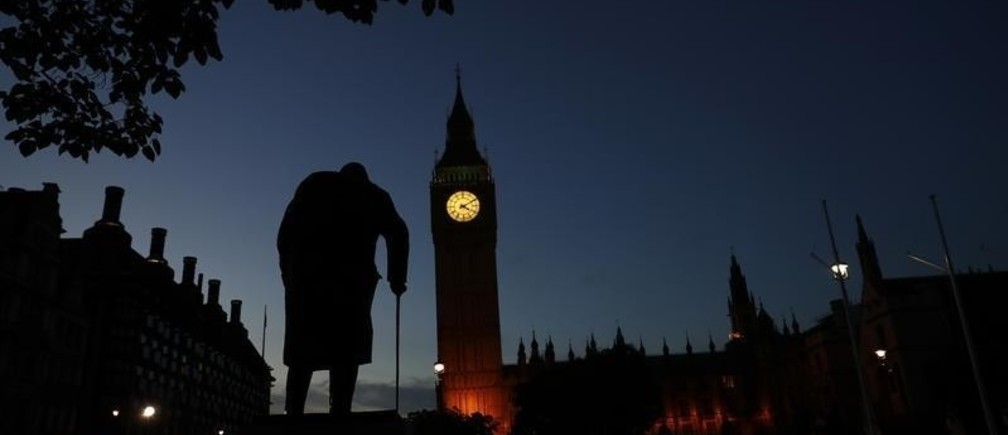 Dawn breaks behind the Houses of Parliament and the statue of Winston Churchill in Westminster.