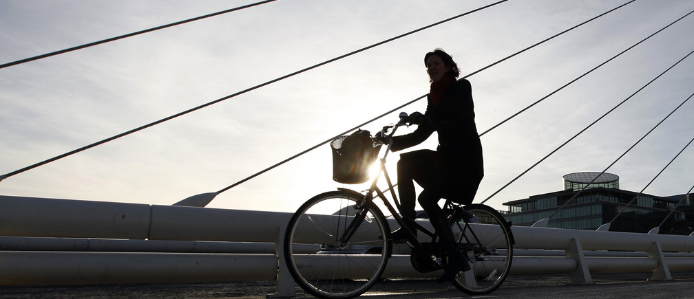 A woman cycles through the financial district of Dublin, February 24, 2011.