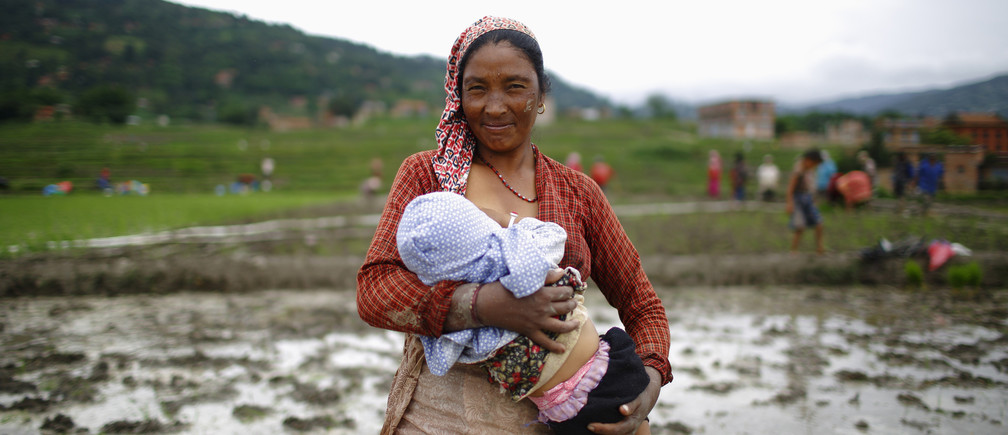 A Nepalese farmer breastfeeds her child before planting rice saplings in a rice paddy field during Asar Pandra festival in Bhaktapur June 29, 2013. Rice is considered the main staple for Nepalese and is planted during the Nepali month of Asar, which usually lies between June and July, typically seen by locals as an auspicious month for planting rice.