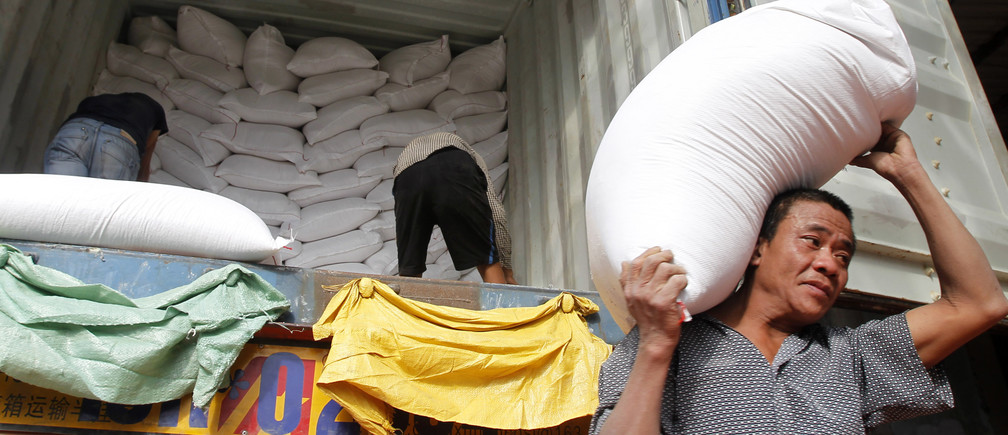 Workers unload bags of rice from a container to a store outside Hanoi November 26, 2013.  Vietnam submitted the lowest price to supply 500,000 tonnes of rice to the Philippines, beating Thailand's offer for grain to boost stocks depleted by Typhoon Haiyan, Manila's grain procurement agency said on Tuesday. Vietnam, the world's second-biggest rice exporter after India last year, offered to deliver the entire volume within three months at $462.25 per tonne, with a first shipment of at least 120,000 tonnes by Dec. 31. REUTERS/Kham (VIETNAM - Tags: BUSINESS FOOD AGRICULTURE) - GM1E9BQ1L6V01