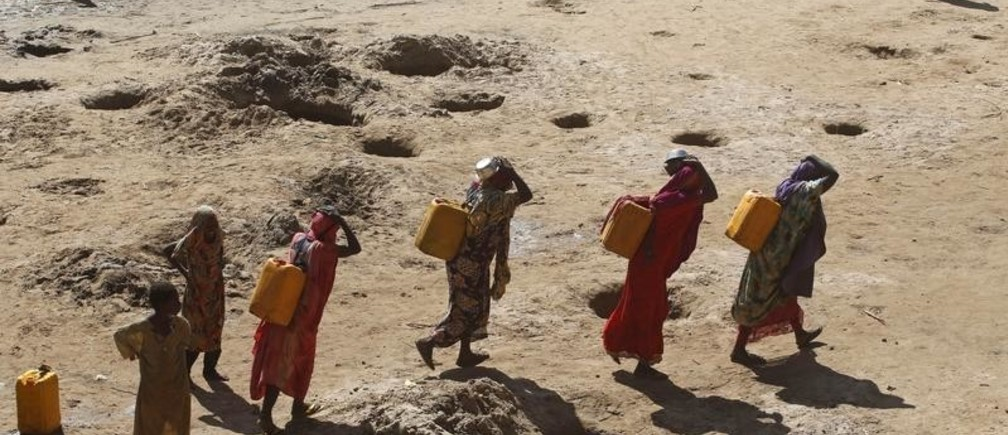 Women carry jerry cans of water from shallow wells dug from the sand along the Shabelle River bed, which is dry due to drought in Somalia's Shabelle region, March 19, 2016. REUTERS/Feisal Omar TPX IMAGES OF THE DAY      - GF10000351737