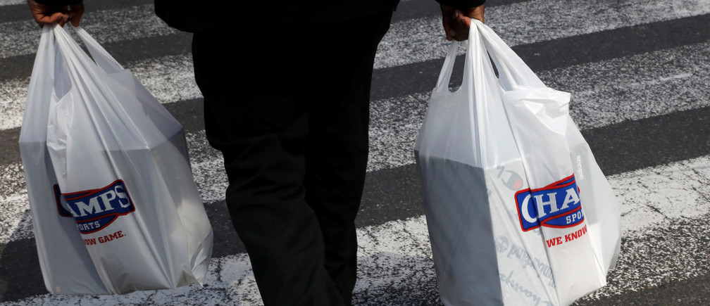 A man carries plastic shopping bags after the New York State legislature included a statewide ban on the use of single use plastic bags in their 2020 budget in Manhattan in New York City, New York, U.S., April 2, 2019. REUTERS/Mike Segar - RC1955CD4160