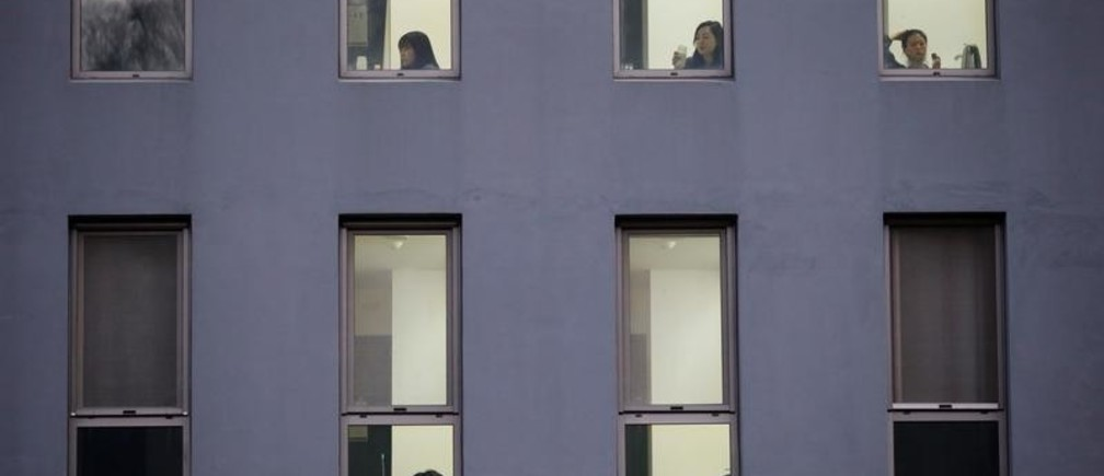 Participants are seen through the windows of Prison Inside Me, a mock prison facility, in Hongcheon, South Korea, November 10, 2018. Since 2013, the facility has hosted more than 2,000 inmates, many of them stressed office workers and students seeking relief from South Korea's demanding work and academic culture.    REUTERS/Kim Hong-Ji - RC13D532F510