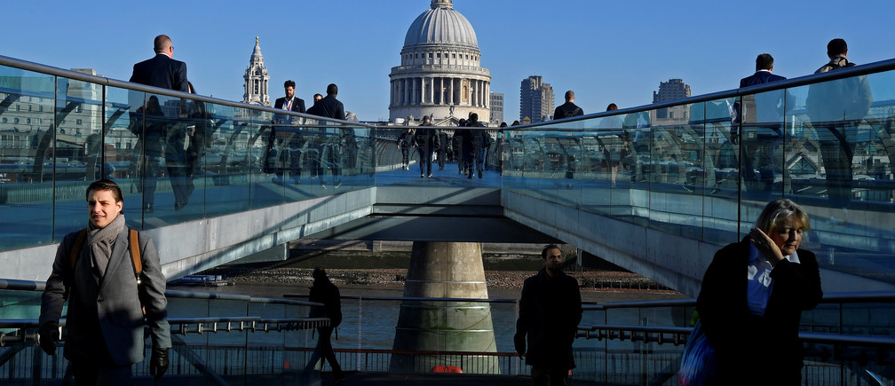 Workers are seen crossing the Millennium Bridge, with St Paul's Cathedral seen behind during the morning rush hour in London, Britain, September 25, 2018. Picture taken September 25, 2018. To match Exclusive BRITAIN-EU/CITY  REUTERS/Toby Melville - RC13569F4470