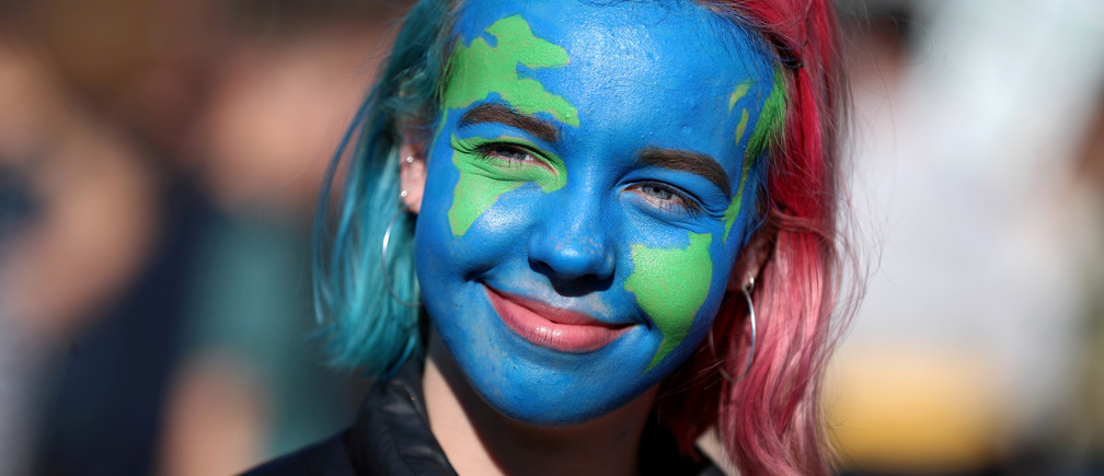 "A girl looks on as people take part in a ""youth strike for climate change"" demonstration in London, Britain February 15, 2019"