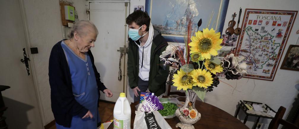 Bastien Gambaudo, joven miembro de la asociación de vecinos El Comité de la Vieja Niza, lleva bolsas de supermercado a una anciana mientras ofrece ayuda para la compra a las personas mayores y aisladas que viven en la vieja ciudad de Niza, durante un encierro impuesto para reducir el ritmo de la enfermedad coronavirus (COVID-19) en Francia, el 26 de marzo de 2020.