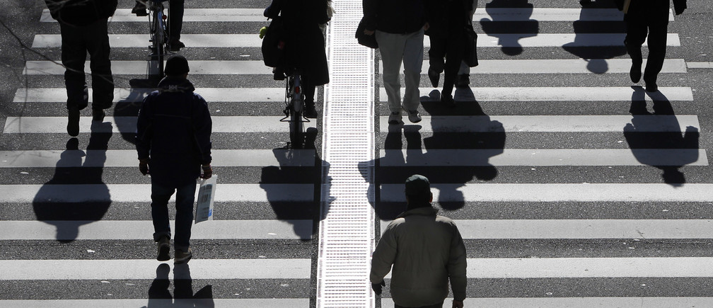 People walk on a crosswalk in Tokyo January 11, 2011. Japan's index of coincident economic indicators rose a preliminary 1.4 points in November from the previous month, the Cabinet Office said on Tuesday, up for the first time in three months. REUTERS/Yuriko Nakao (JAPAN - Tags: EMPLOYMENT BUSINESS) - GM1E71B15WJ01