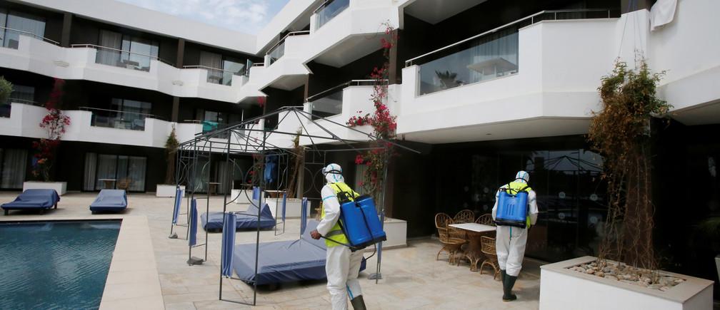 Trabajadores con trajes protectores desinfectan el hotel Dawliz, que se utiliza como lugar de refugio temporal para todo tipo de material médico con el fin de aumentar el distanciamiento social durante el brote de la enfermedad coronavirus (COVID-19) en Sale, Marruecos. 24 de abril de 2020.